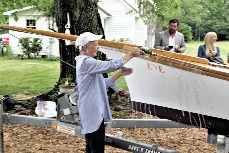Eve Love christens her namesake, Eve, a 20-foot log canoe, in a launching ceremony held recently in Drayden, MD. Photo by Rick Franke