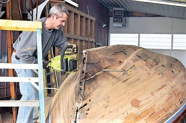 Project manager, Vincent Roe, removes the rotten keel on the log canoe, JAY DEE at Campbell's Boatyard in Oxford, MD.