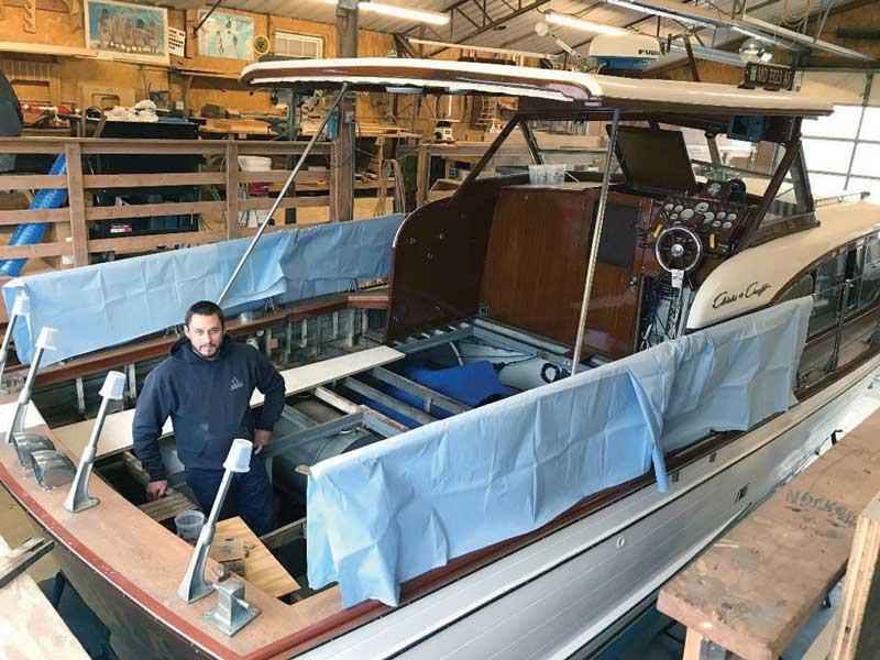 Jared Satchell working on a teak deck replacement on a classic Chris-Craft at Campbell's Boat Yard in Oxford, MD.