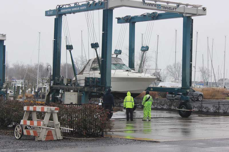 Winter haul outs must go on despite the cold winter rain at Herrington Harbour North in Tracys Landing, MD. Photo by Rick Franke