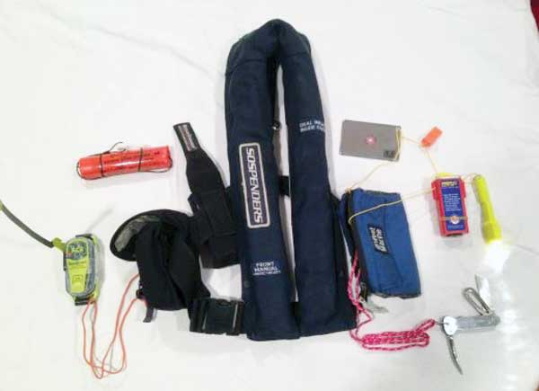 An inflatable PFD with personal equipment: PLB, streamer, mirror (for signaling), whistle, strobe light, flashlight, and knife. Perhaps add personal pen flares for offshore passages. Photo courtesy Kip Louttit