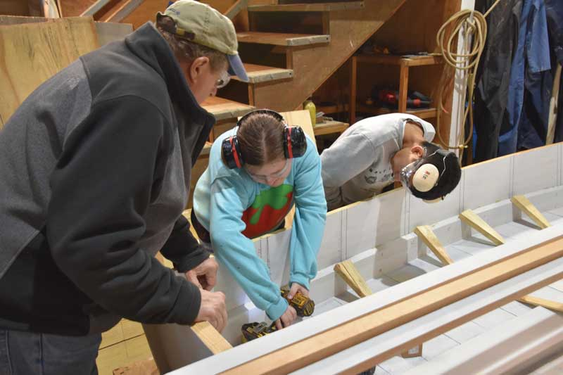 Rising Tide volunteer Ned Henninghausen supervises program participants Ava Reid and Jonathan Storch working on the 17-foot skiff Mary at the Chesapeake Bay Maritime Museum's shop in St. Michaels, MD.