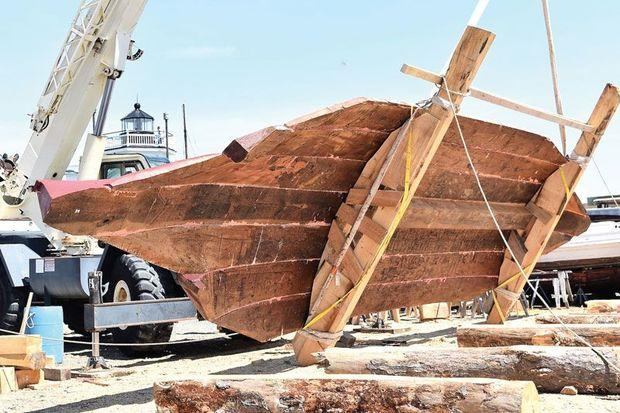 The seven-log bottom for the bugeye Edna W. Lockwood being flipped over by a crane at the Chesapeake Bay Maritime Museum in St. Michaels, MD.