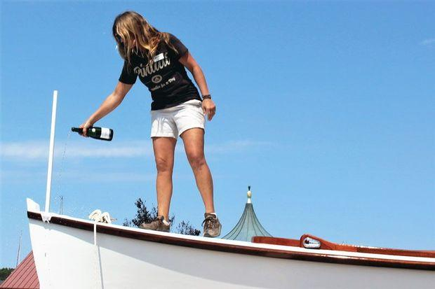 Boat yard program manager Jenn Kuhn christens Pintail in the traditional way with champagne.