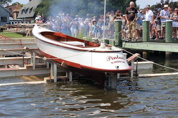 The draketail Pintail touches water for the first time at her launching at Chesapeake Bay Maritime Museum. The smoke is from a celebratory cannon fired in her honor.