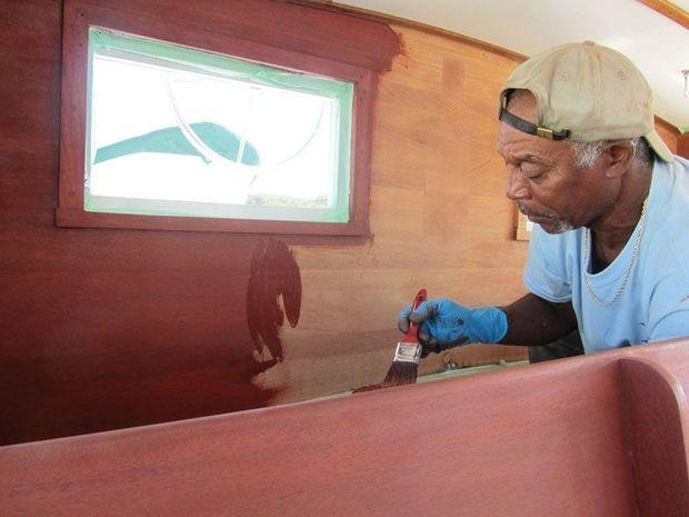 Peany Matthews applies stain to the interior of the wheel house on a Wiley 40 at Hartge Yacht Yard in Galesville, MD.