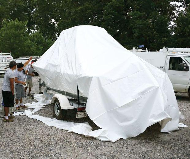Staff at Diversified Marine Services in Annapolis shrinkwrapping a boat on its trailer.