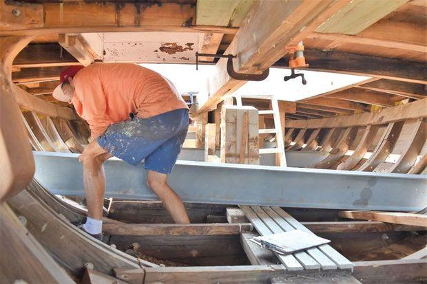 Shipwright Apprentice Spencer Sherwood helps slide a steel beam through 1889 Edna E. Lockwood at the Chesapeake Bay Maritime Museum in St. Michaels, MD. The beams were used to lift the topsides off the hull.