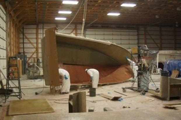 A crew places a layer of fiberglass on the interior hull of a boat as it nears completion. Photo by Gary Reich.